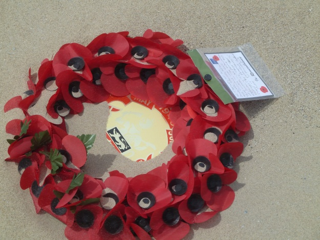 A wreath laid to commemorate the 75th anniversary of the evacuation, blown by the wind onto the sand.